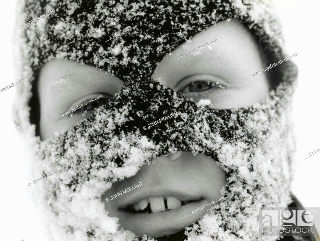 Stock Photo: Close-up of boy in ski mask, covered with snow.