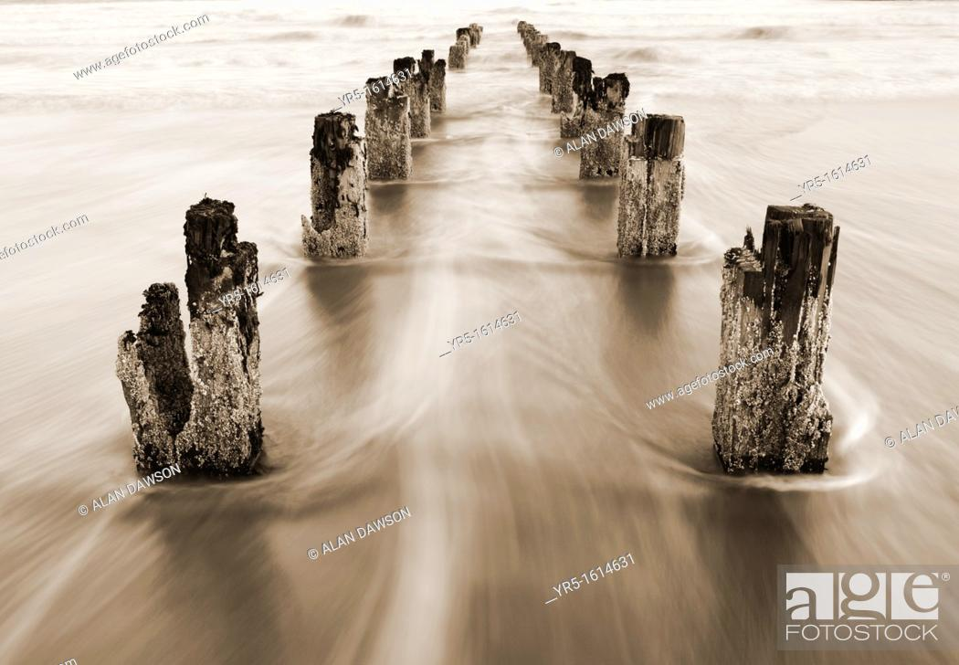 Stock Photo: Receeding tide flowing around wooden posts.