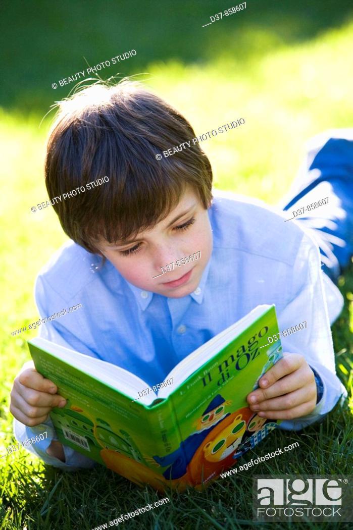 Stock Photo: Boy enjoying reading a book in the garden.