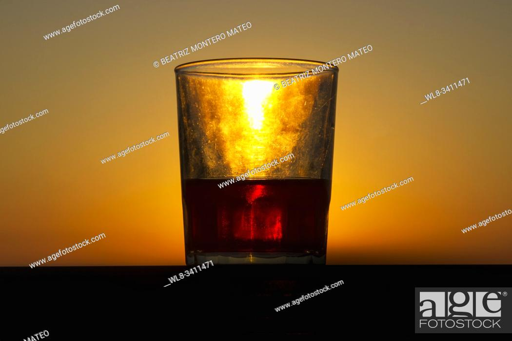 Stock Photo: Sunset in Menorca's beach (Baleares, Spain). Awesome lights in the sunset with a crystal glass.