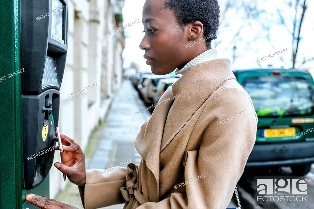 Stock Photo: France, Paris, Young woman paying with her smartphone at parking automat.