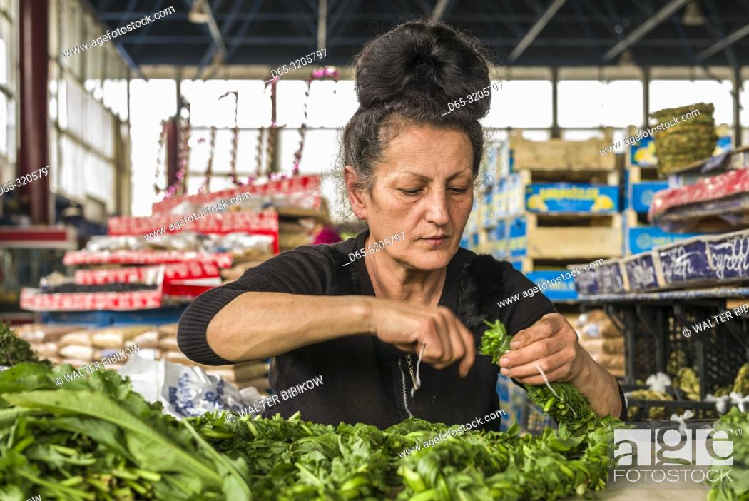 Imagen: Armenia, Yerevan, G. U. M. Market, food market hall, woman braiding sorrel, MR.