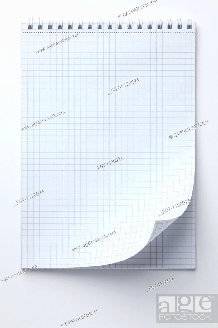 Stock Photo: A spiral notepad with graph paper and a curled up page corner.