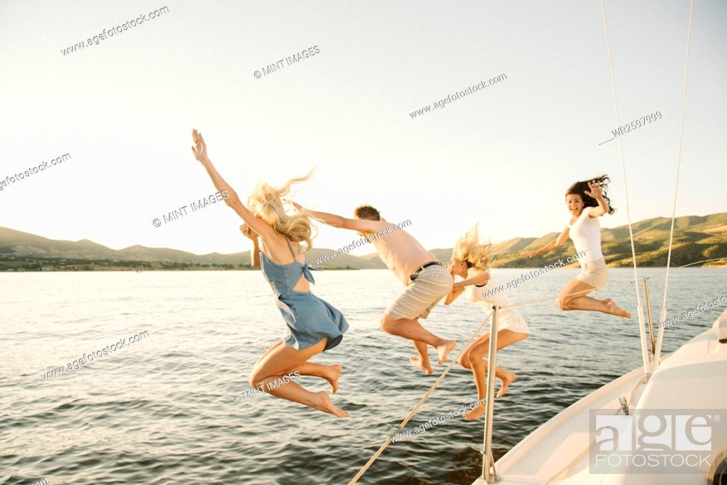 Imagen: Four people jumping off the side of a sail boat into a lake.