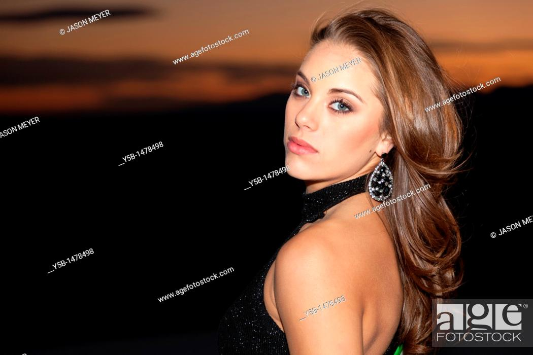 Stock Photo: Pretty woman in black dress looking over shoulder during sunset.
