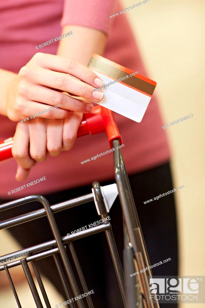 Stock Photo: Germany, Cologne, Young woman holding credit card in supermarket.