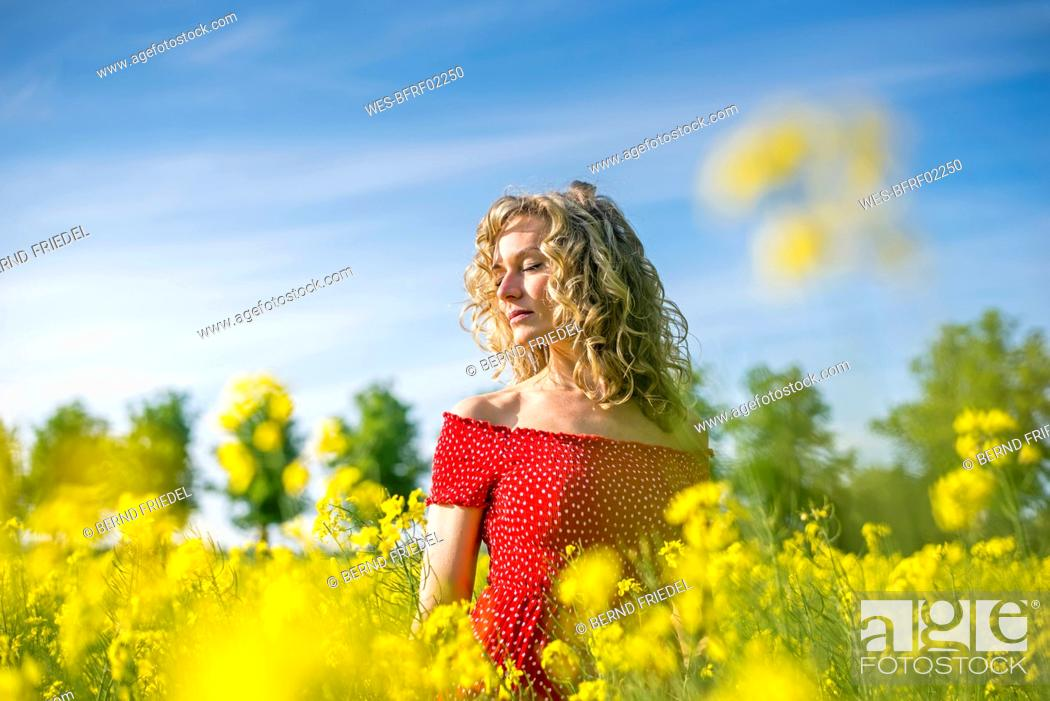 Stock Photo: Woman wearing red dress with eyes closed standing amidst oilseed rapes.