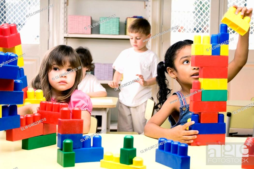 Stock Photo: Two girls playing with plastic blocks with their friends in the background.