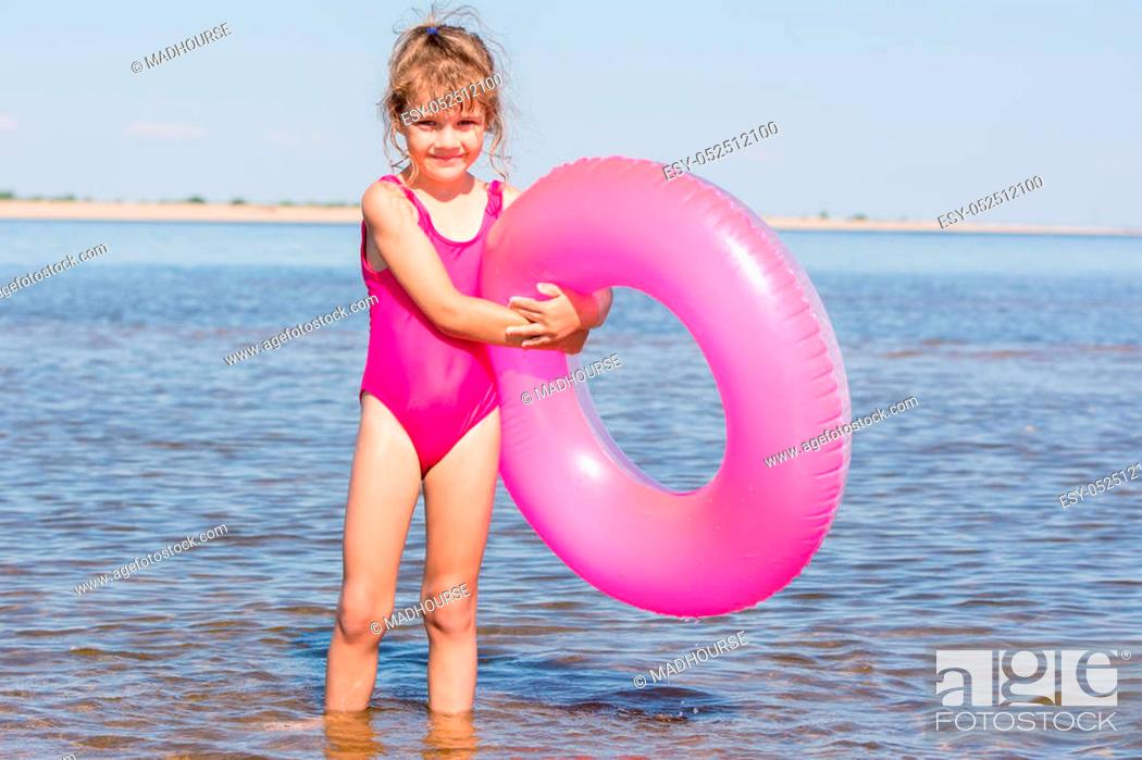 Stock Photo: Five-year girl in a pink bathing suit standing with swimming laps in the river.