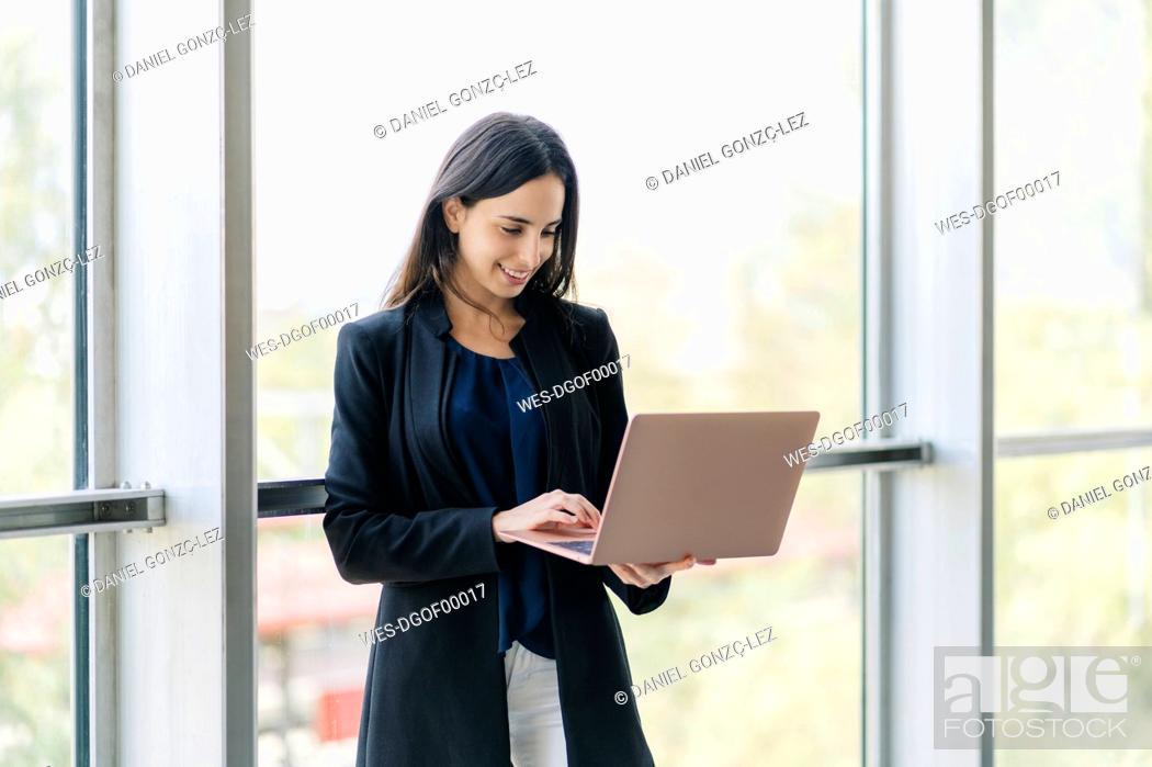 Stock Photo: Smiling businesswoman using laptop.