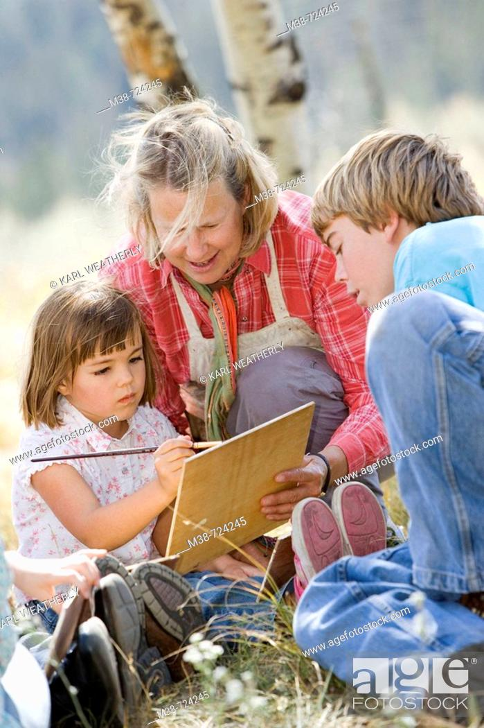 Stock Photo: Woman teaching kids to paint, Lone Mt Ranch, Big Sky, Montana, USA.