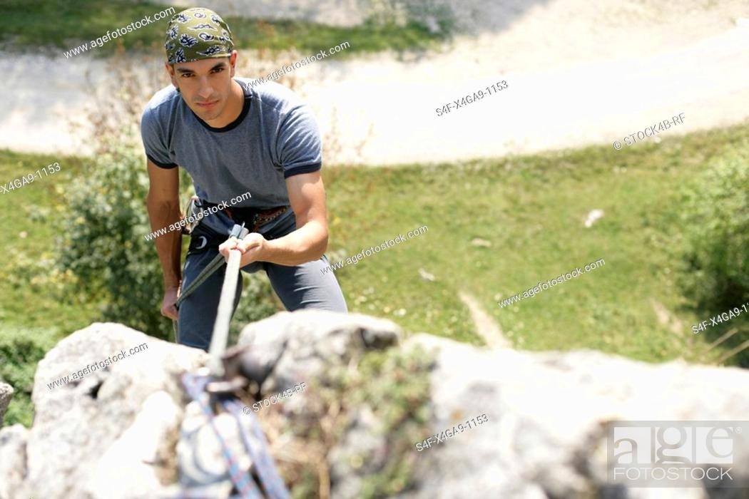 Stock Photo: Young man with a bandana climbing up a rocky wall, selective focus.
