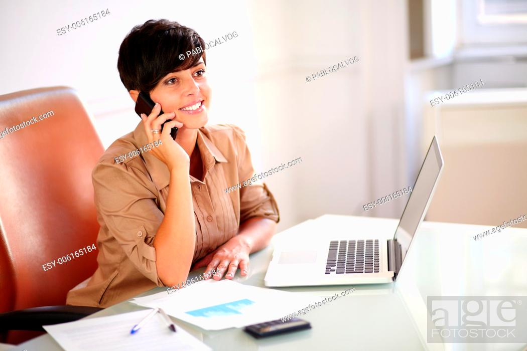 Stock Photo: Portrait of a beautiful businesswoman talking on her cellphone while sitting on employee desk.