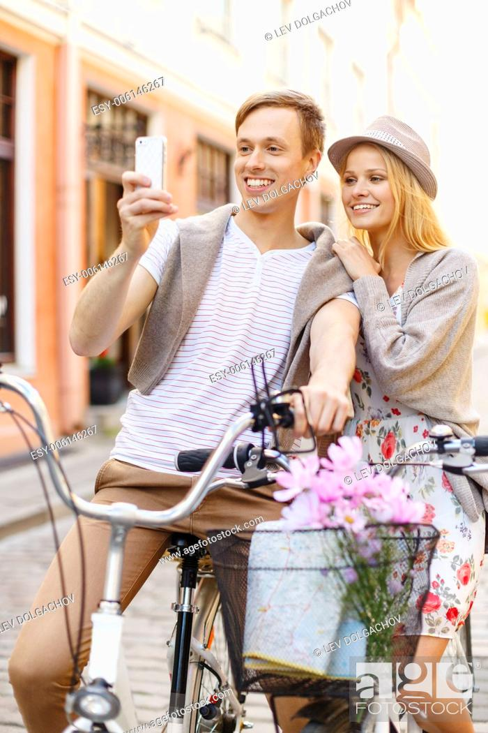 Stock Photo: summer holidays, bikes, love, relationship, navigation, gps and dating concept - smiling couple with bicycles and smartphone in the city.