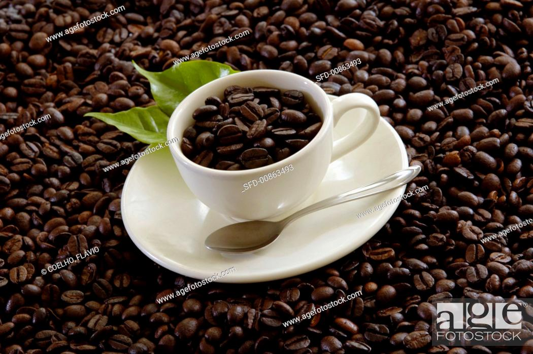 Stock Photo: Coffee beans in a cup and forming the background.