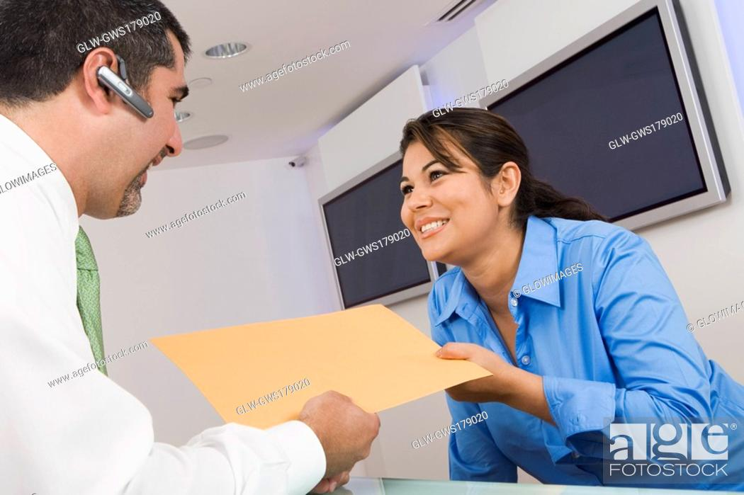 Stock Photo: Receptionist giving a file to a businessman.