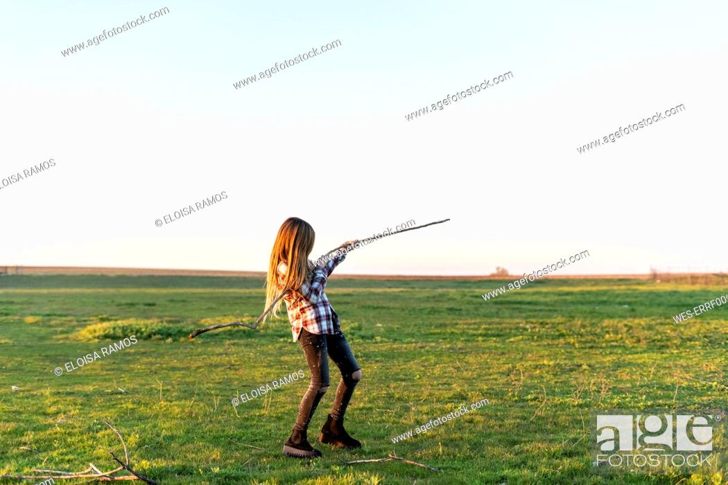 Stock Photo: Girl playing with stick in nature.