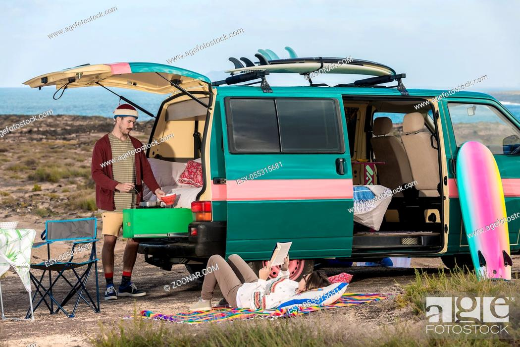 Photo de stock: Woman reading book and man cooking meal in camping van having trip through Lanzarote island, Spain.