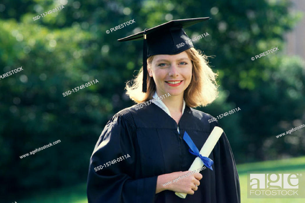 Stock Photo: Portrait of a young woman wearing a graduation outfit holding a diploma.
