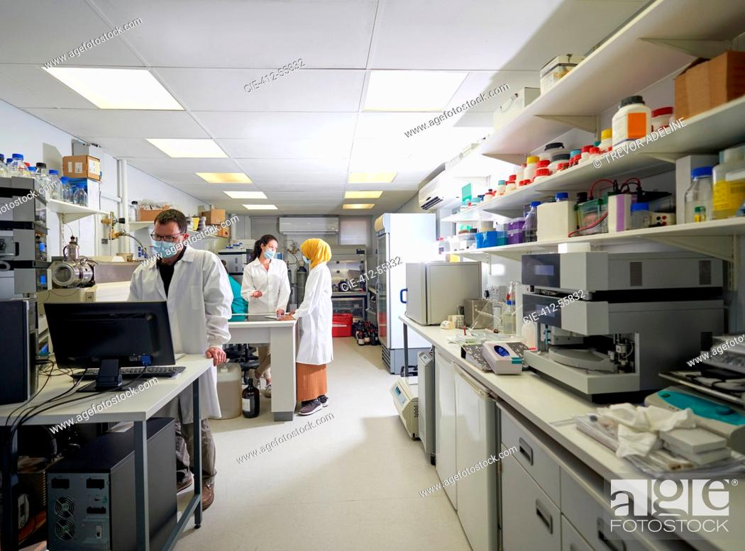 Stock Photo: Scientists in face masks working in laboratory.