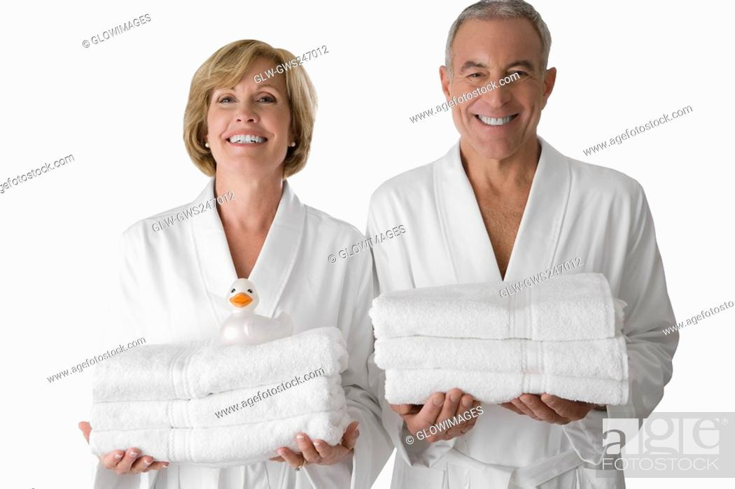 Stock Photo: Portrait of a senior man with a mature woman standing together and holding folded towels.