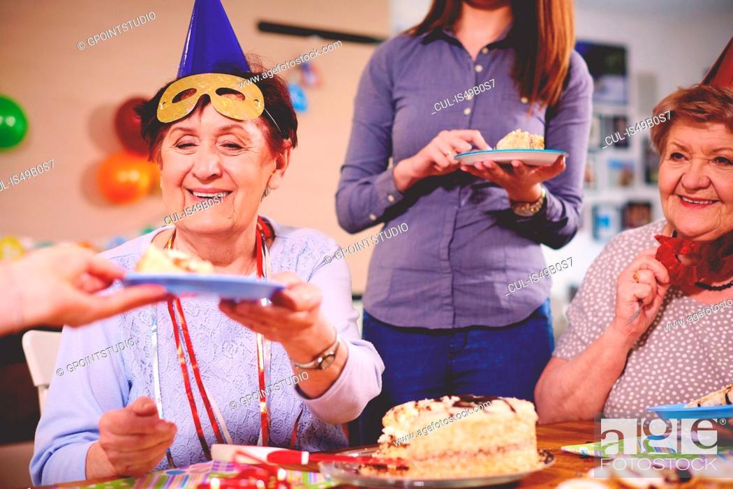 Stock Photo: Senior women being served birthday cake at party.