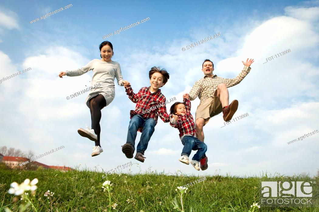 Stock Photo: A family holding hands and jumping in the air.