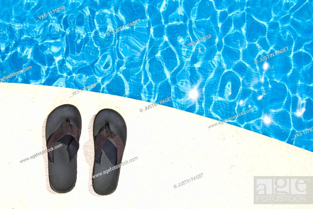 Stock Photo: Shot of a Pair of Flip Flops next to the Pool.