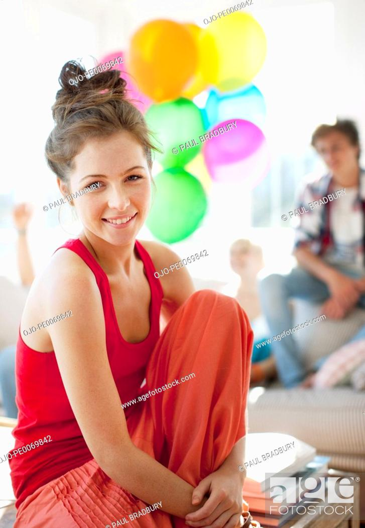 Stock Photo: Woman smiling with friends holding balloons in background.
