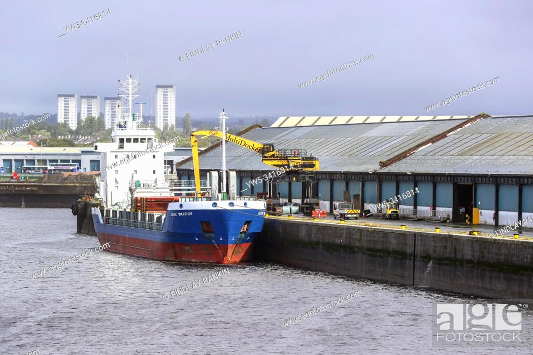 Stock Photo: Cargo ship being unloaded at a pier at King George V docks, Glasgow, Scotland, UK.