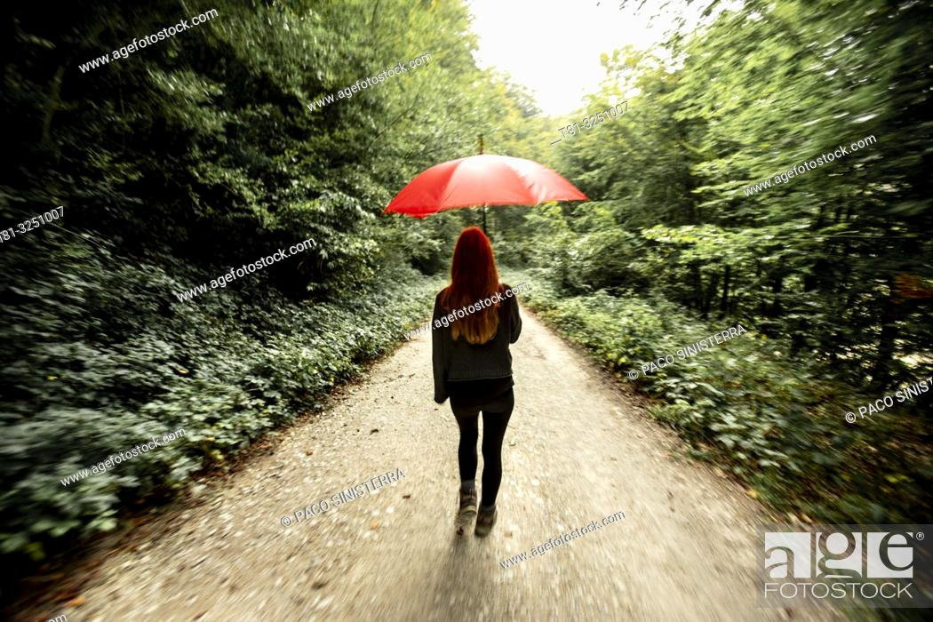 Stock Photo: Girl walking through the forest with red umbrella, Navarra. Spain.
