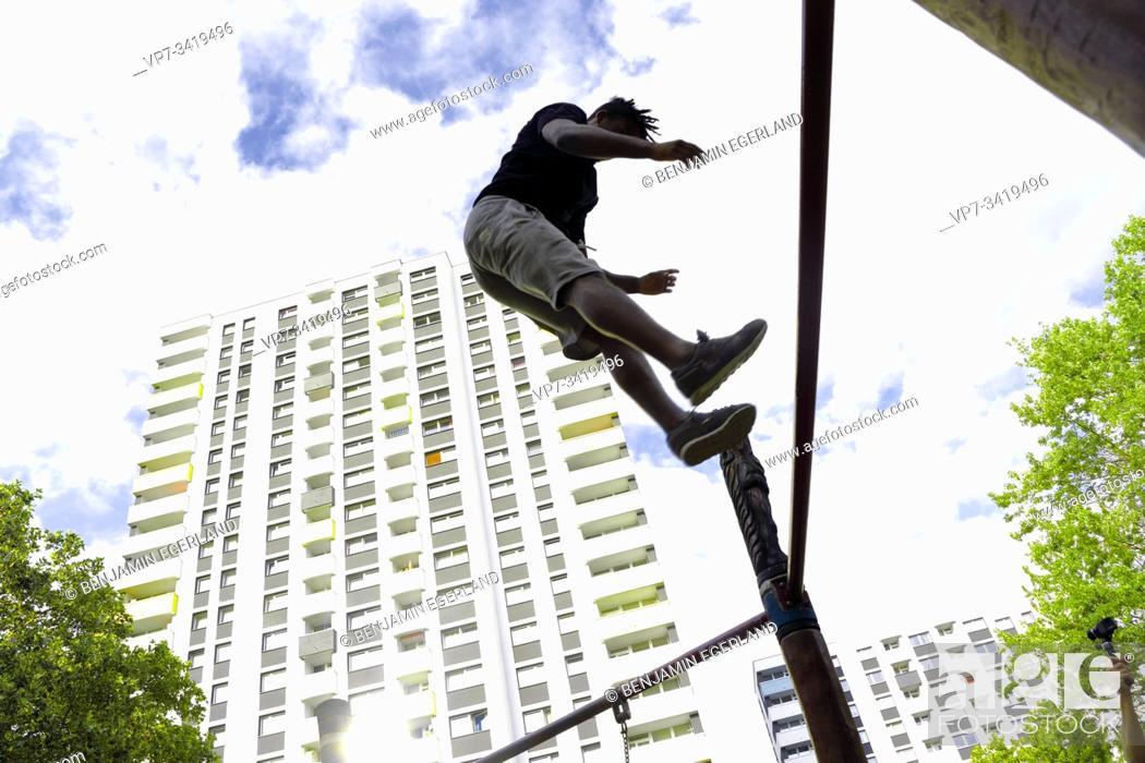 Stock Photo: Young man jumping in park. Frankfurt am Main, Germany.