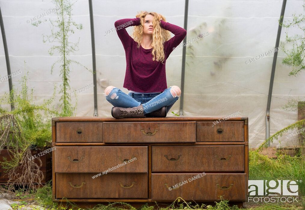 Imagen: Portrait of a caucasian teenage girl with long blond, curly hair sitting cross-legged on a weathered dresser inside a greenhouse; Apex, North Carolina.