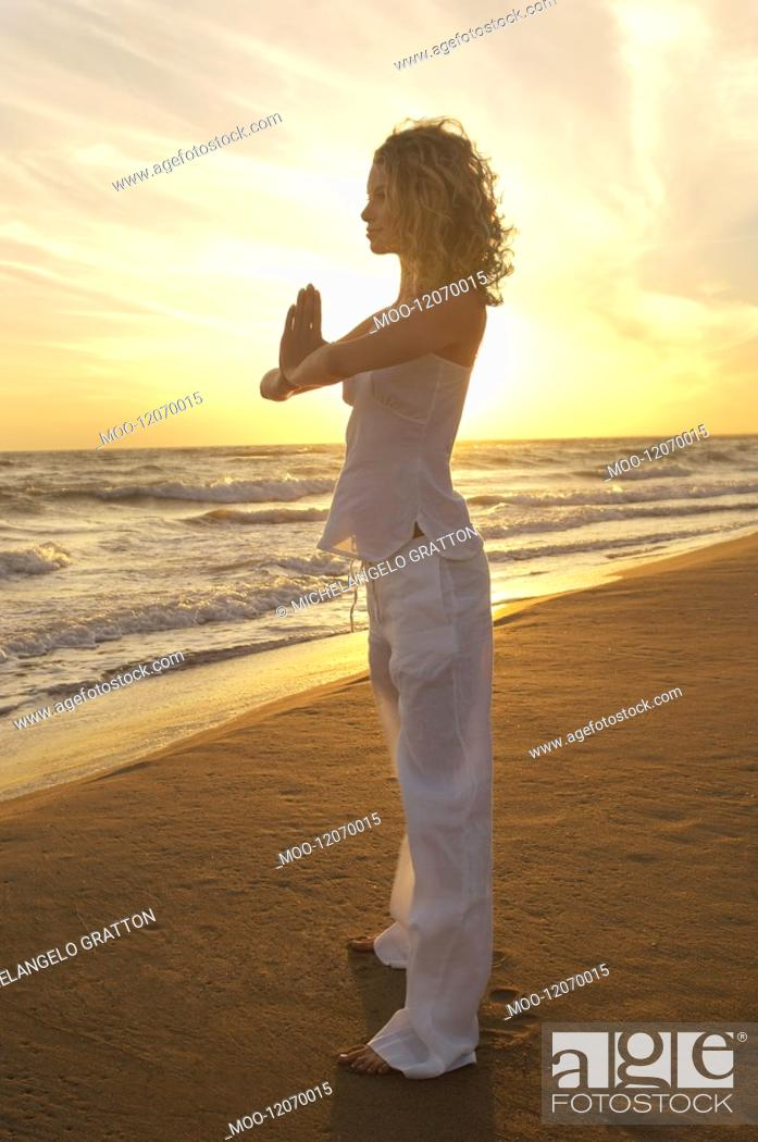 Stock Photo: Young woman doing Tai Chi on beach side view.