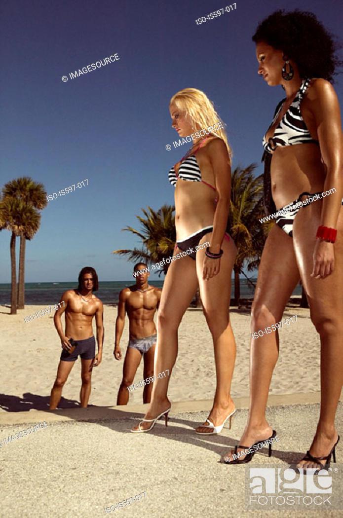 Stock Photo: Men watching women on beach.