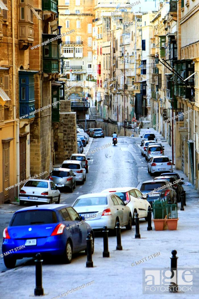 Imagen: Cars parked in street and person riding motor scooter in historic district of Valletta, Malta.