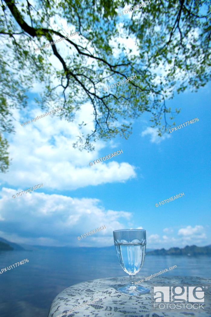 Stock Photo: Glass of water on a table by a lake, Towada, Aomori Prefecture, Japan.
