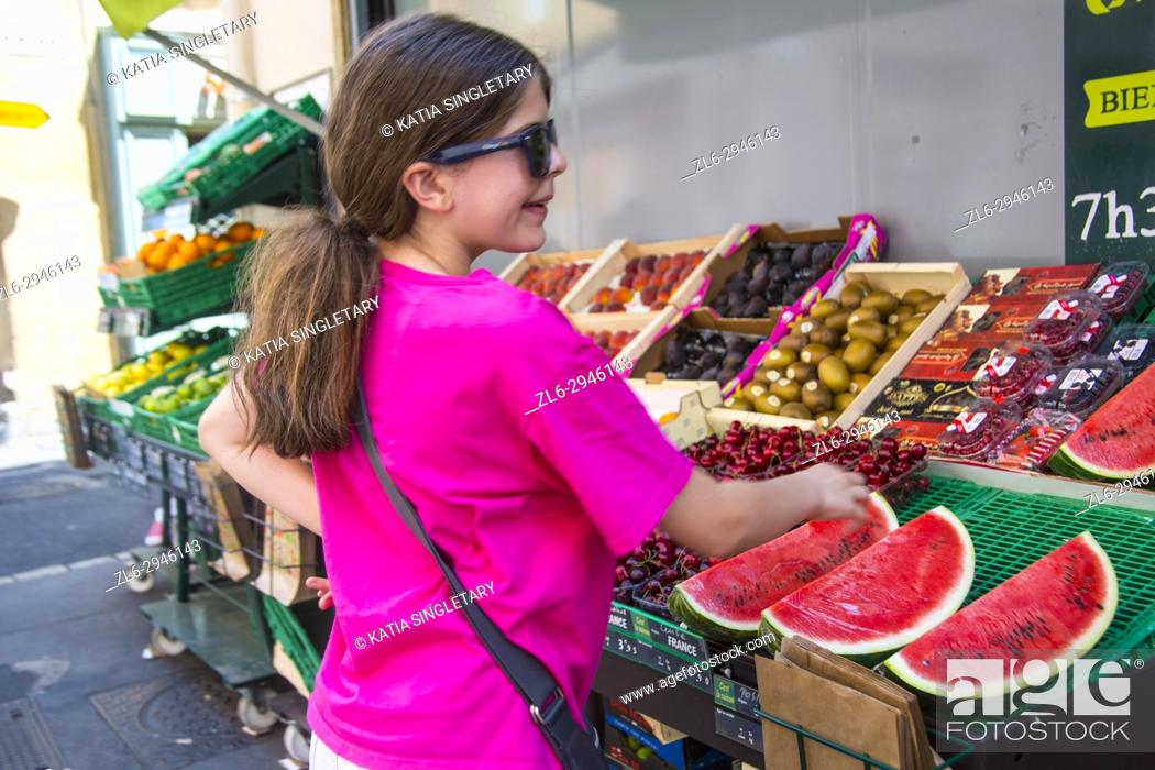 Stock Photo: Young teen, preteen smiling and looking at the outdoor window front store of a local french grocery store.