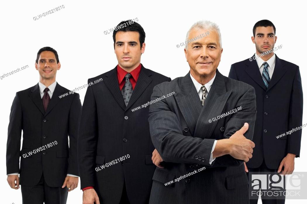 Stock Photo: Portrait of a businessman smiling with three businessmen standing behind him.