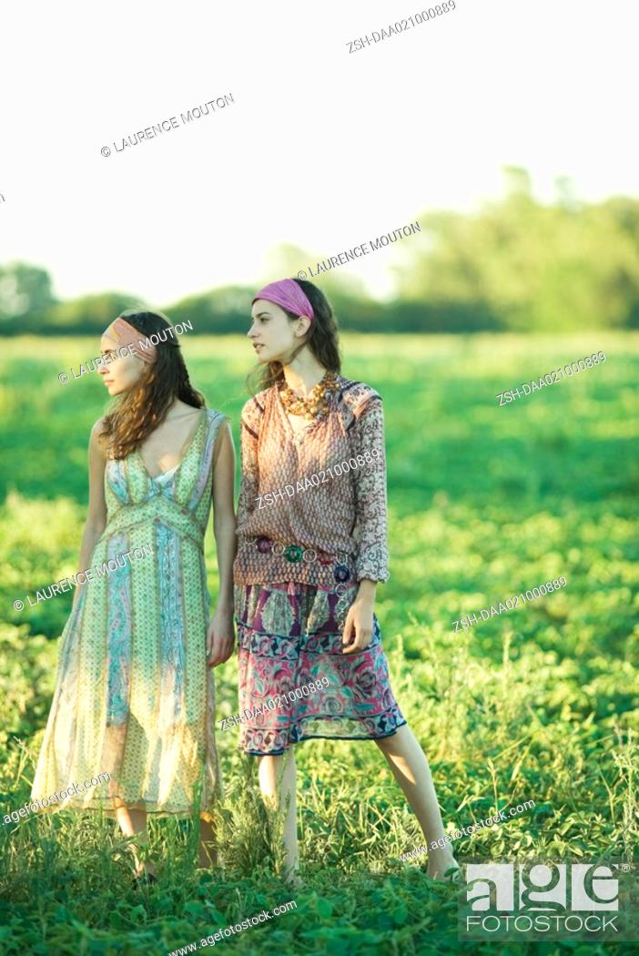 Stock Photo: Young hippie women standing in field, looking away, full length.