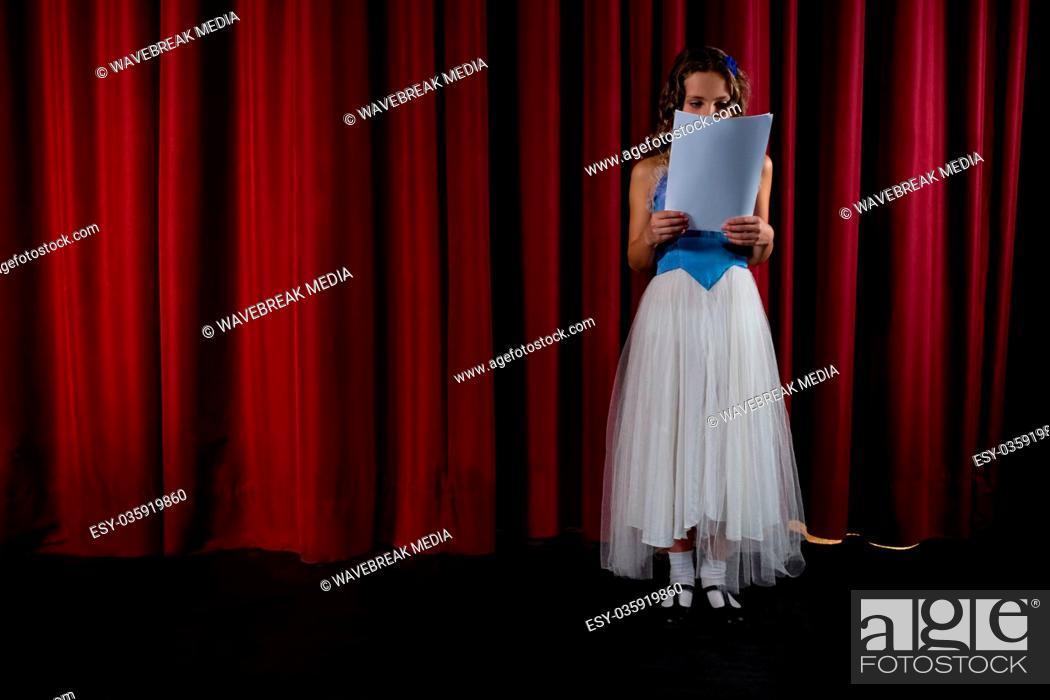 Imagen: Female artist reading her scripts on stage.