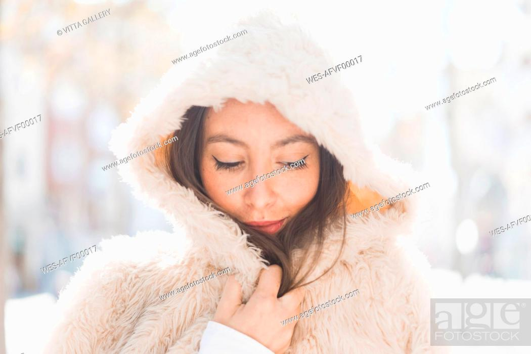 Stock Photo: Portrait of young woman wearing hooded fur jacket.