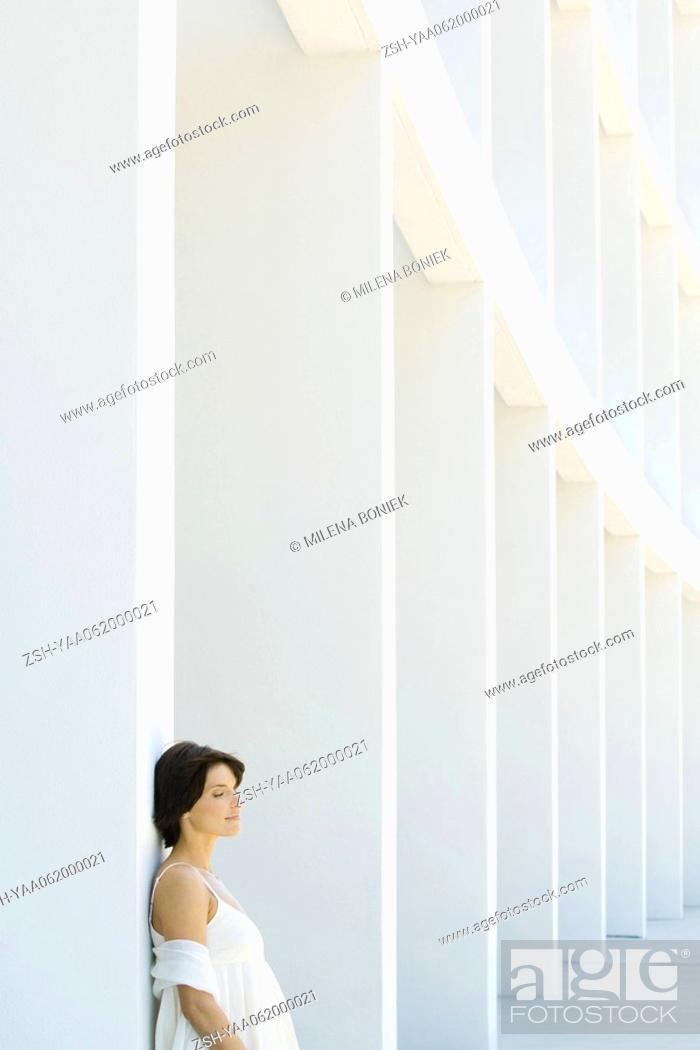 Stock Photo: Woman leaning against column with eyes closed, side view.