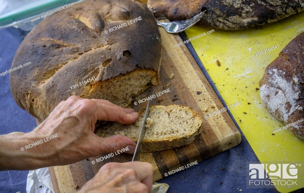 Stock Photo: A baker cuts a slice of artisanal bread baked in a wood-fired oven in Brooklyn in New York on Sunday, August 19, 2018. (© Richard B. Levine).