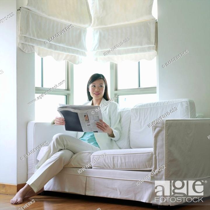 Stock Photo: Businesswoman sitting on a couch with a newspaper in her hand.