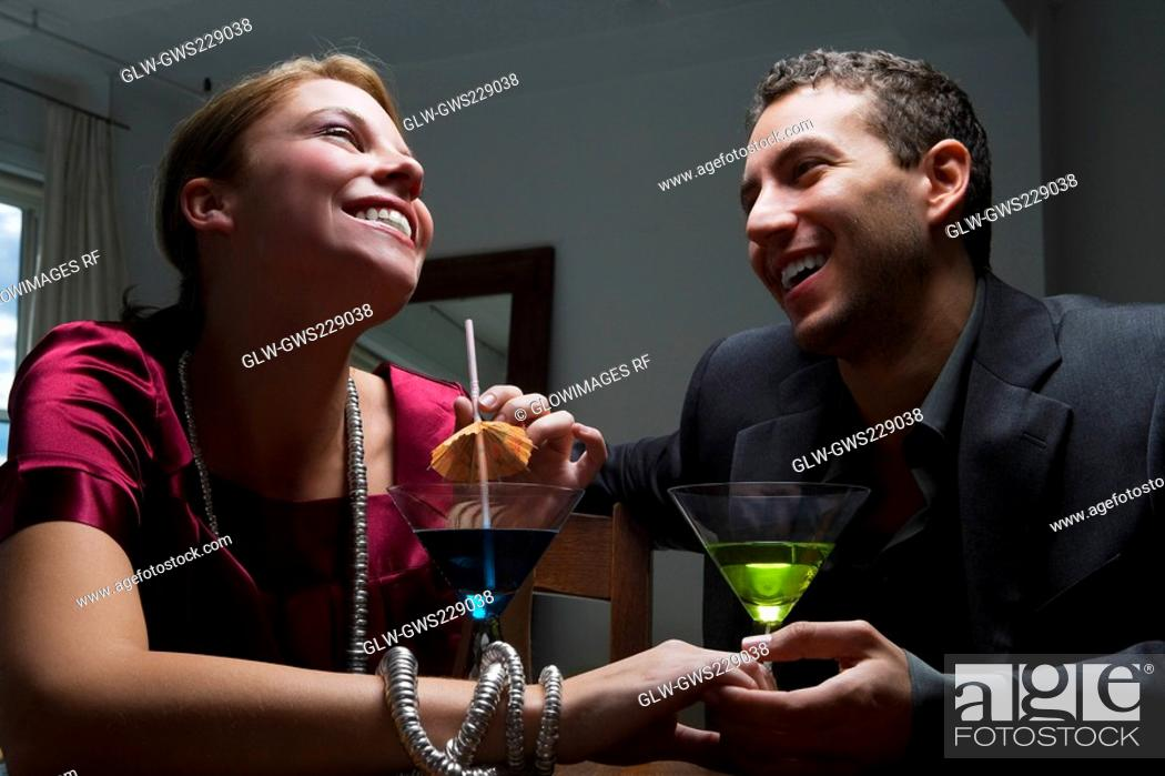 Stock Photo: Young couple drinking cocktail and romancing.