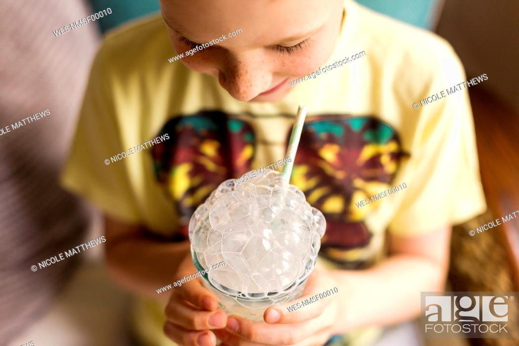Stock Photo: Playful boy making milk bubbles with a straw.