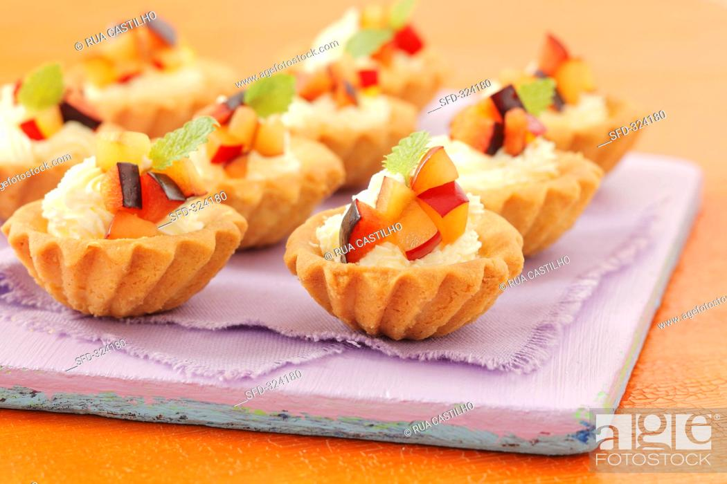 Stock Photo: Tartlets with whipped cream and plums.