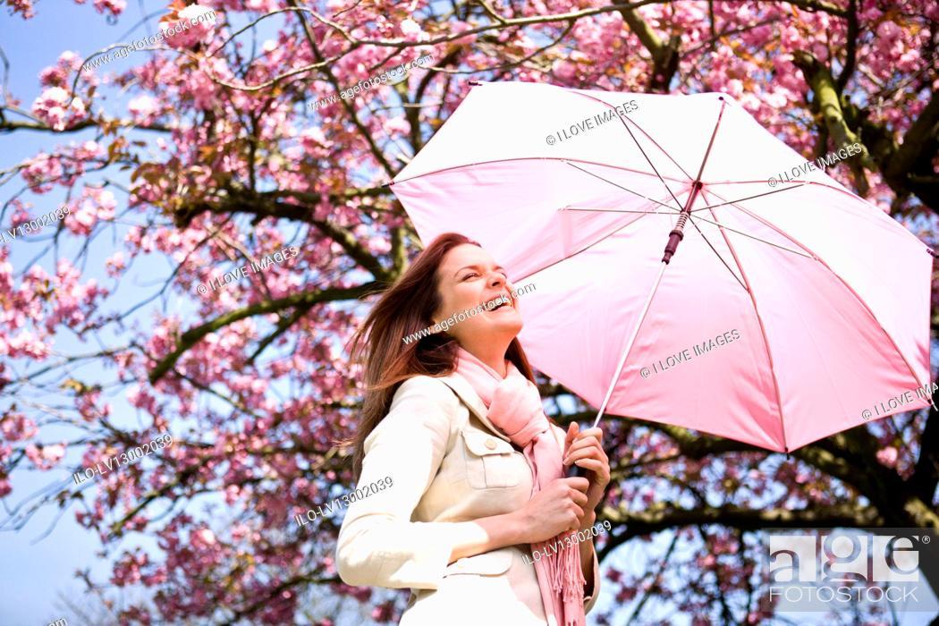 Stock Photo: A young woman holding an umbrella, in springtime.