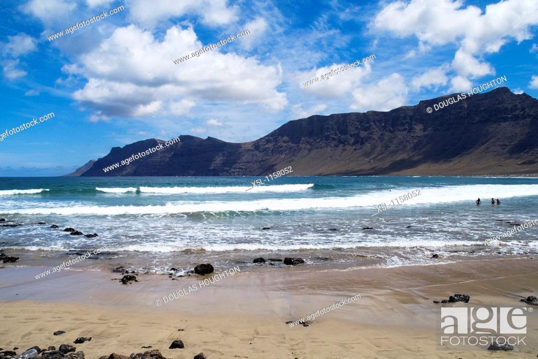Stock Photo: Playa de Famara FAMARA LANZAROTE Bathers in surf waves sandy beach El Risco de Famara sea cliffs and bay.